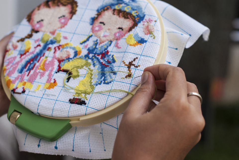Person cross-stitching a design with a needle, hoop, and thread.
