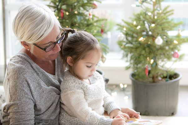 Grandmother Watching Granddaughter Drawing in Front of Christmas Trees