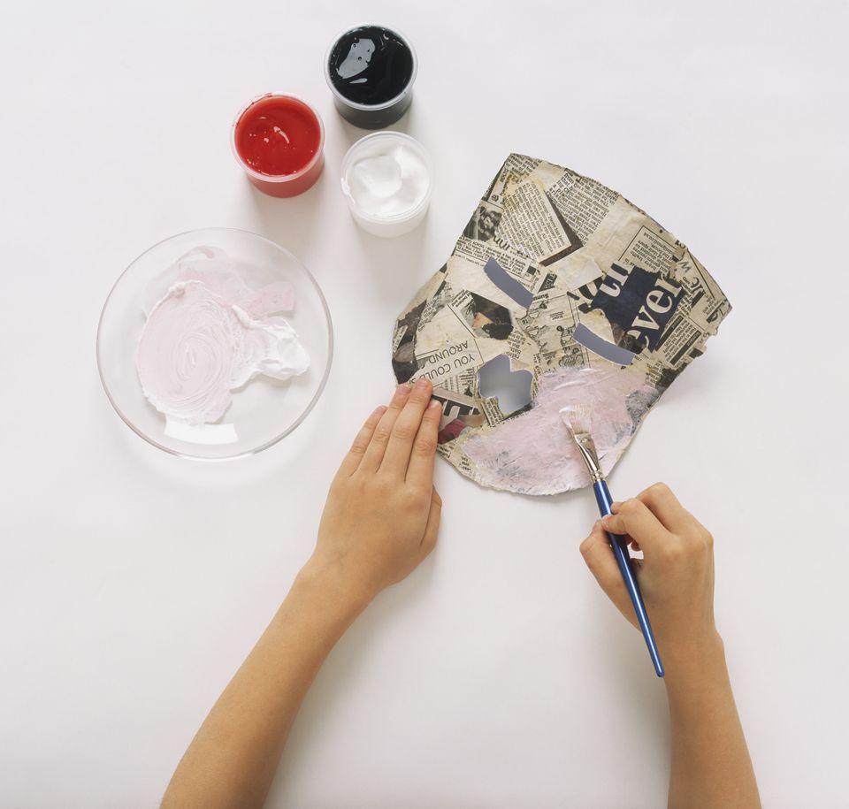 Painting papier-mache mask.