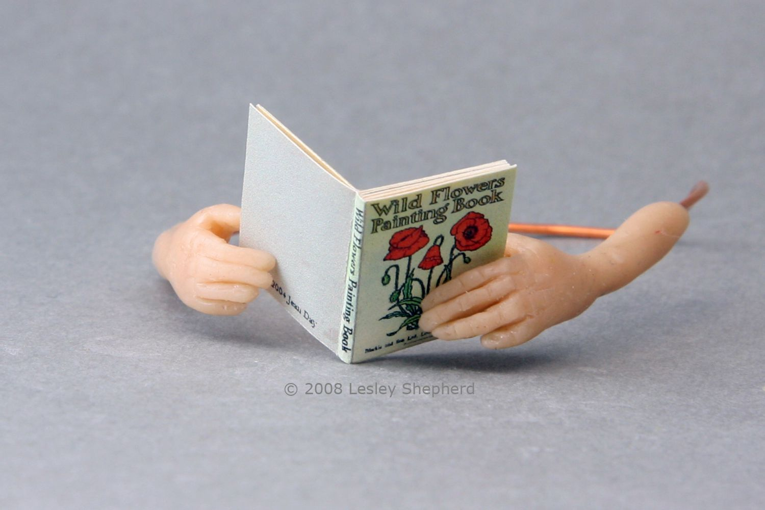1:12 scale miniature doll hands, sculpted from polymer clay with detailed fingers and thumbs, hold a dollhouse book