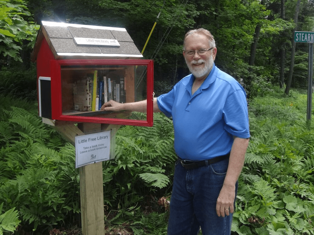 Picture of a man standing next to a little free library