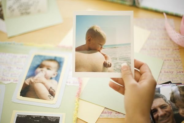 Woman holding baby picture for scrapbook