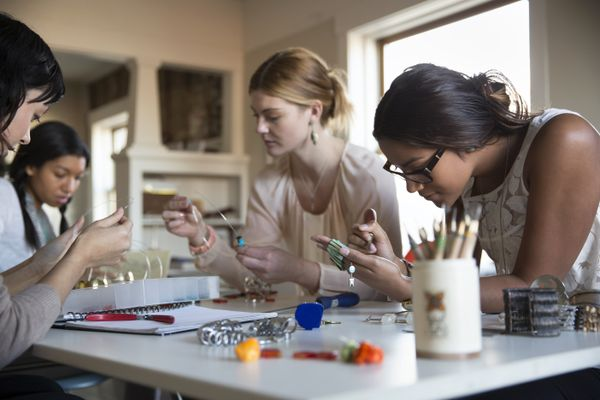 young women making bracelet and necklaces at desk