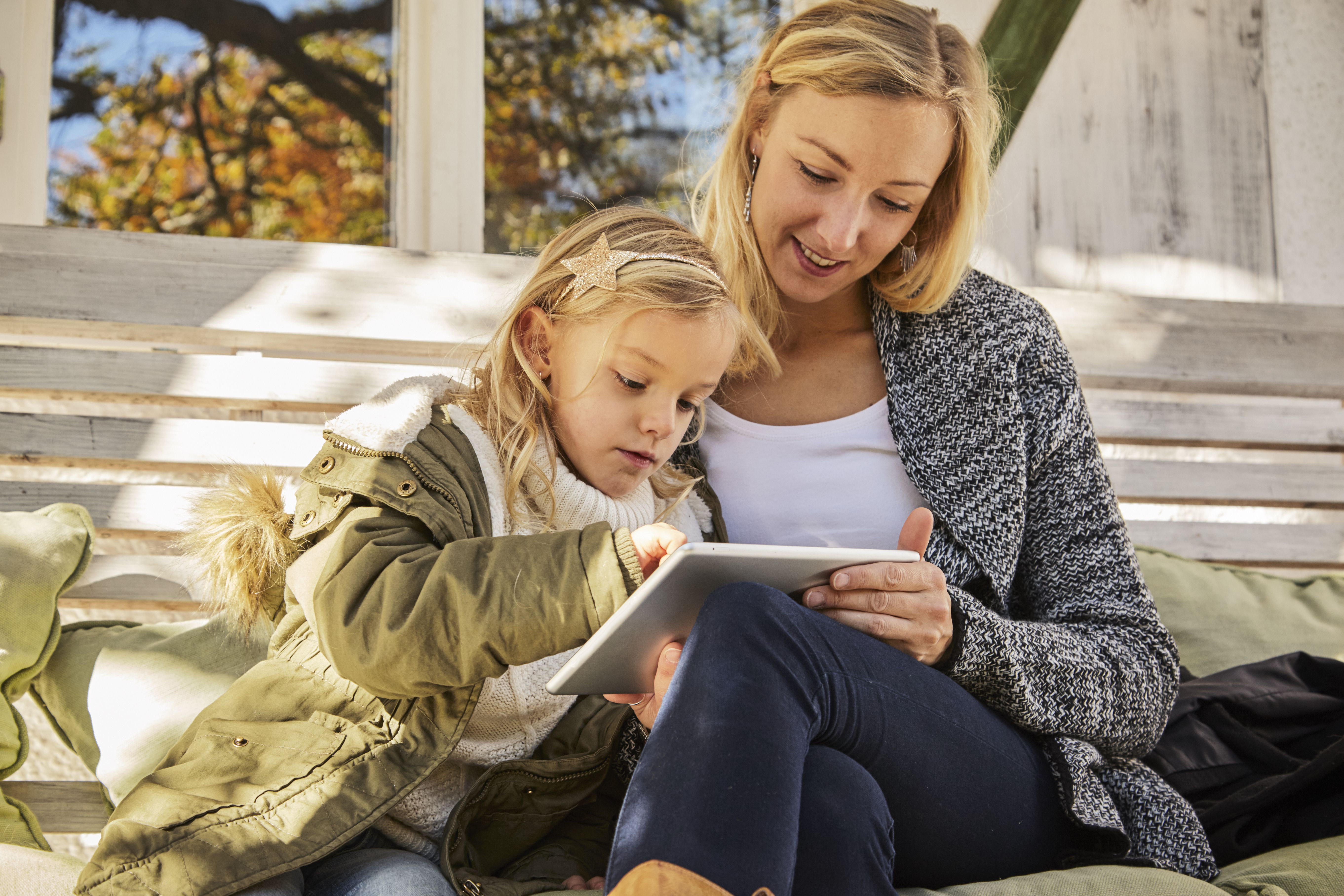 Mother with daughter on bench using tablet