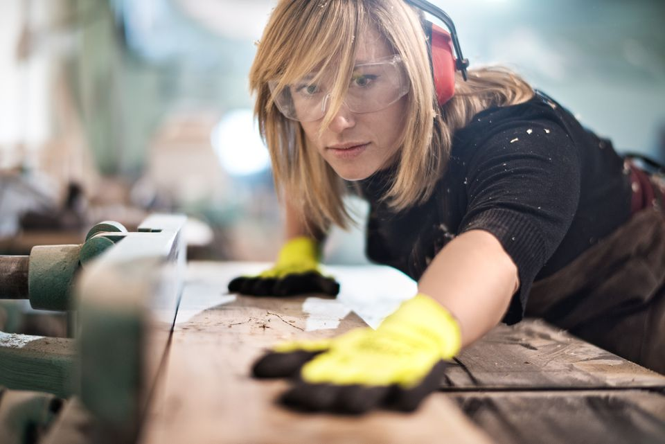 Blonde woman cutting a plank