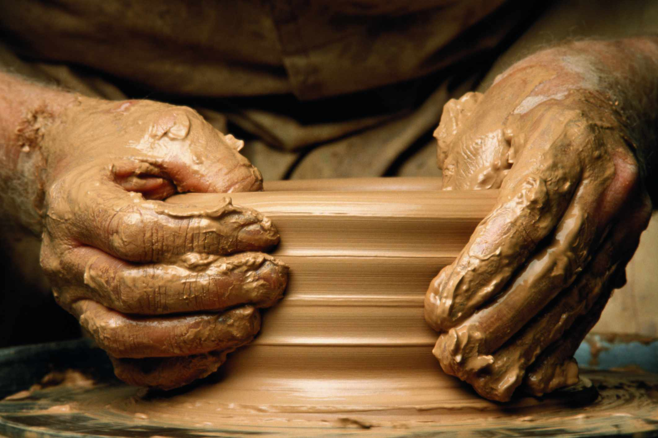 Hands forming clay pot on potter's wheel