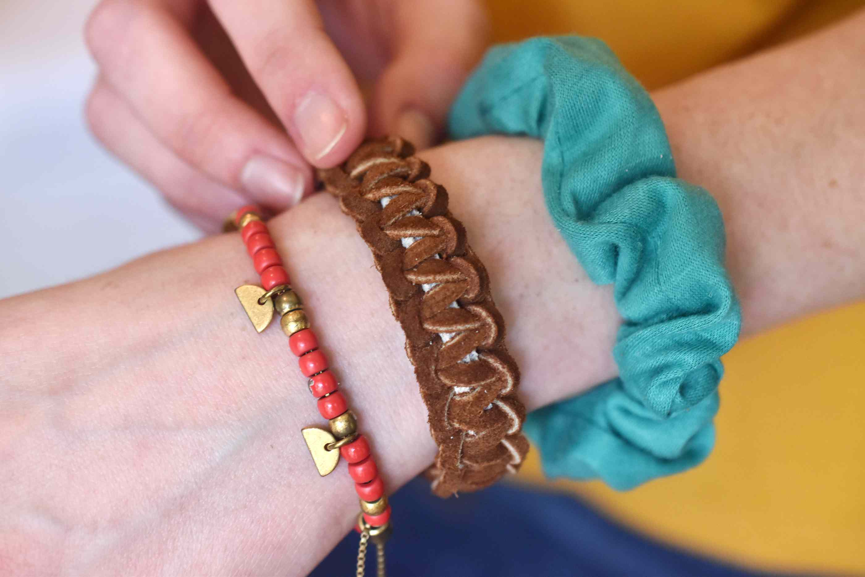Young Woman Wearing a Cobra Knot Bracelet with Scrunchies and Other Jewelry