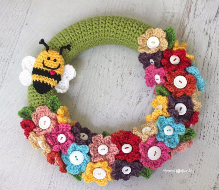 Button flowers and a cute little bee adorn this crochet wreath