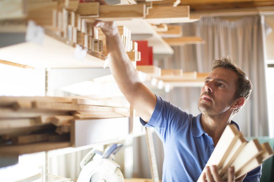 Man taking wood from shelf in workshop