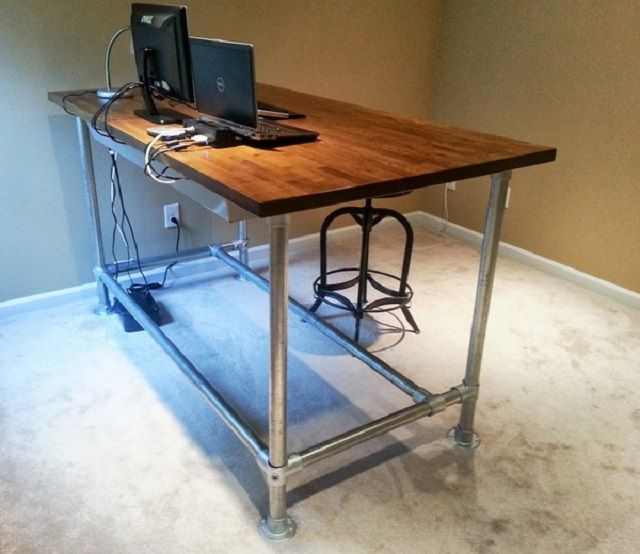 DIY wooden standing desk with silver pipes as legs.