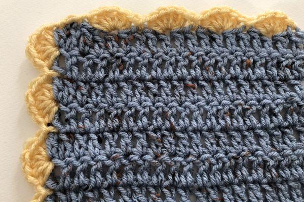 Yellow crochet shell stitch edging around blue yarn.