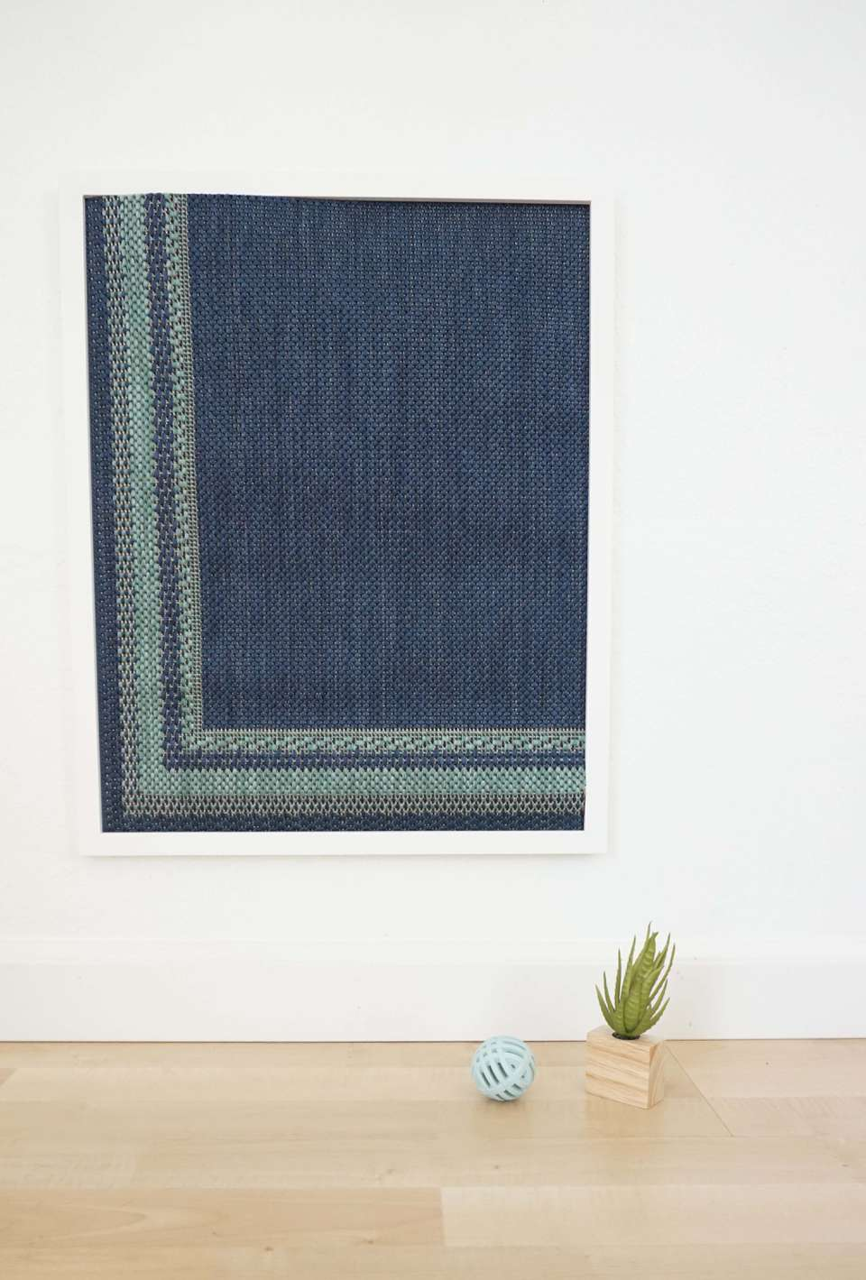 A blue framed rug with a tiny plant and cat toy.
