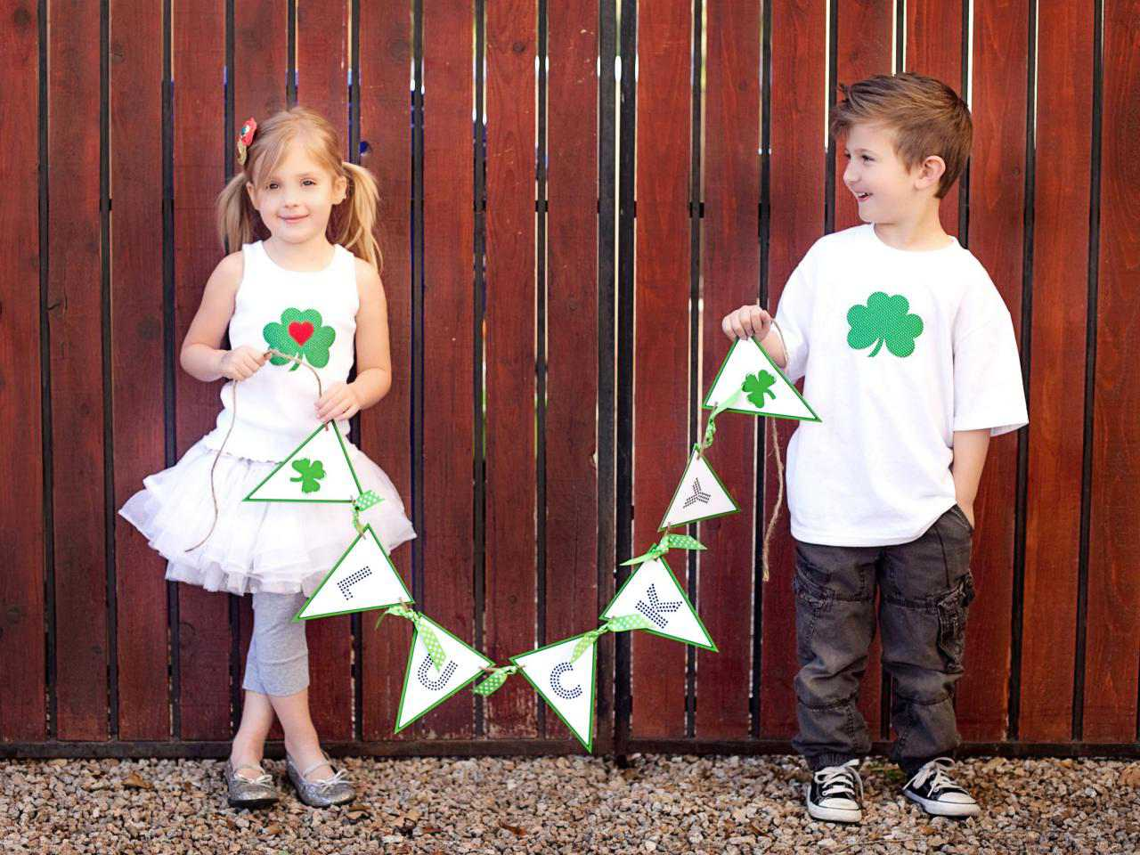 """Two kids holding a """"Lucy"""" St. Patrick's Day banner"""