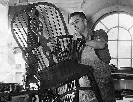 A man French at Messrs Nicholls & James, High Wycombe, Buckinghamshire, polishes a Windsor armchair for export to the USA.