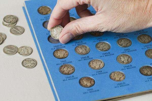 Placing a Mercury dime and a coin folder.
