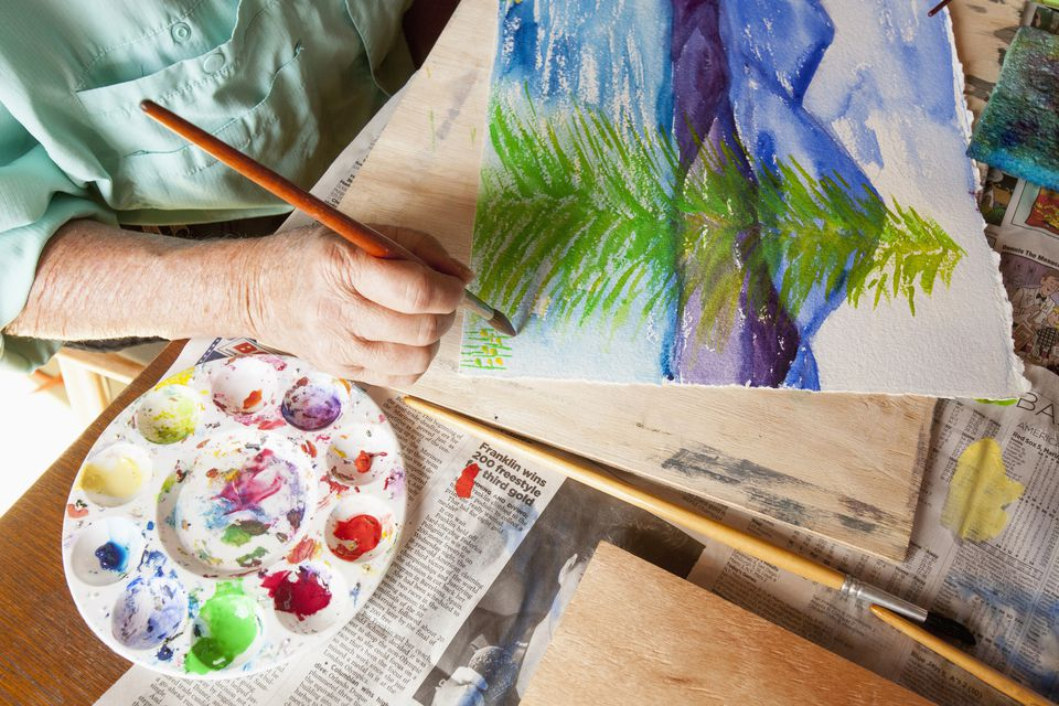 Caucasian artist painting watercolor tree