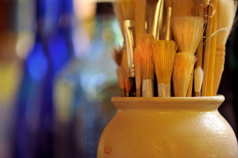 Paintbrushes in jar near the window of an artists studio window