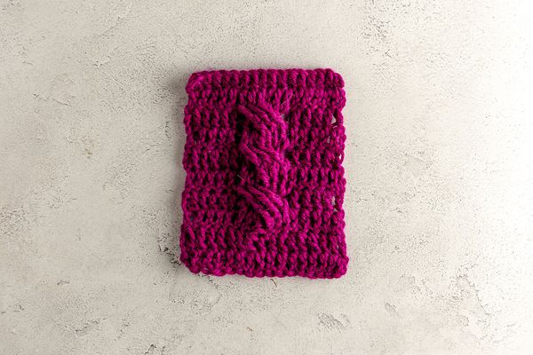 A purple crochet cable stitch swatch on a table.