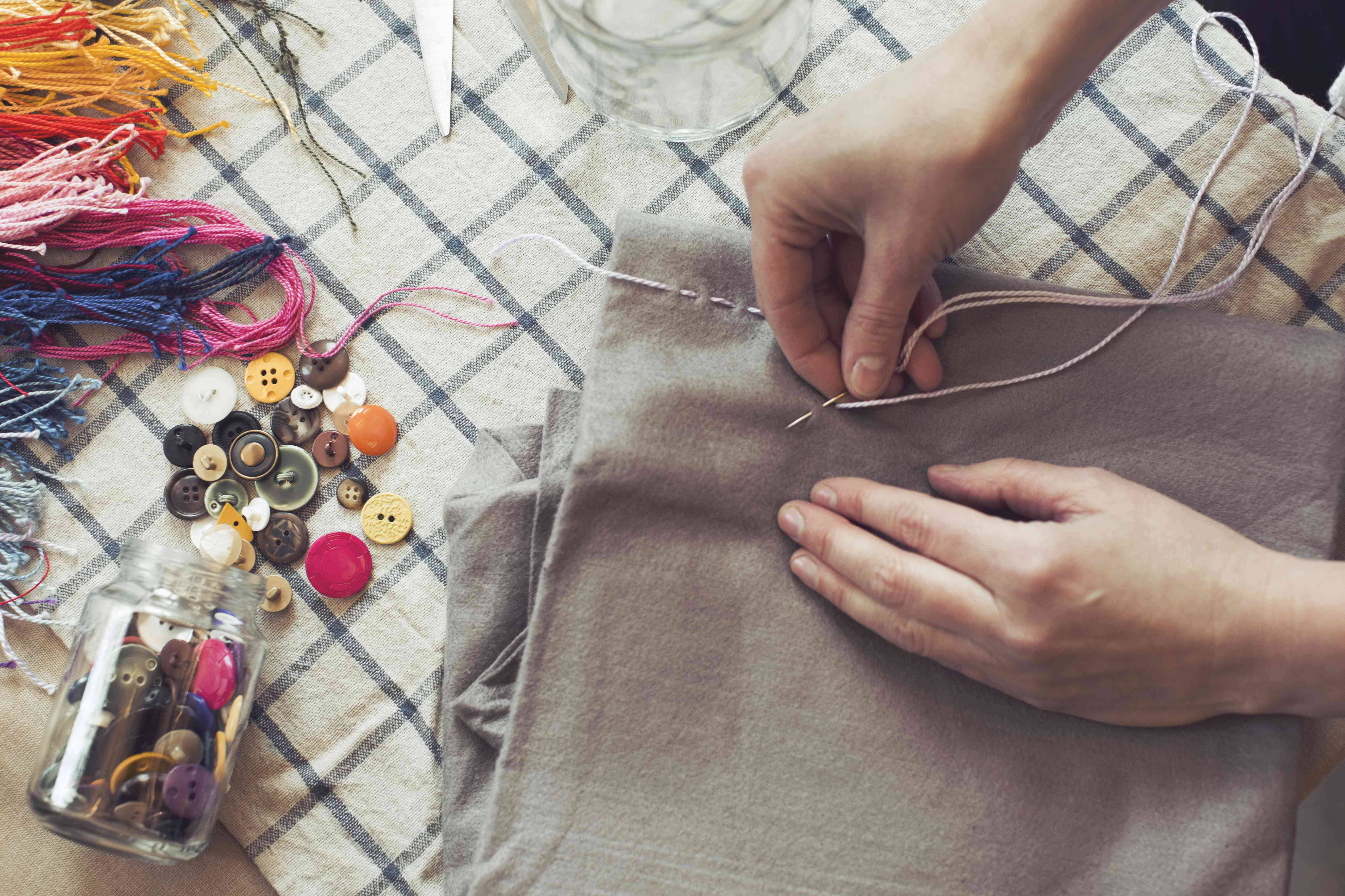 High-angle view of a person stitching fabric