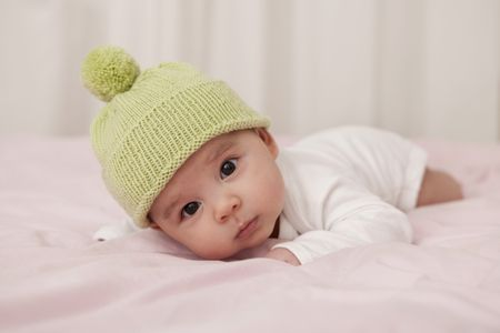 2315032d480 Baby boy wearing wooly hat lying on bed
