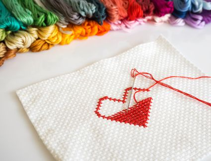 Close up stitching red heart shape on white fabric on white background. With colorful yarn on background.