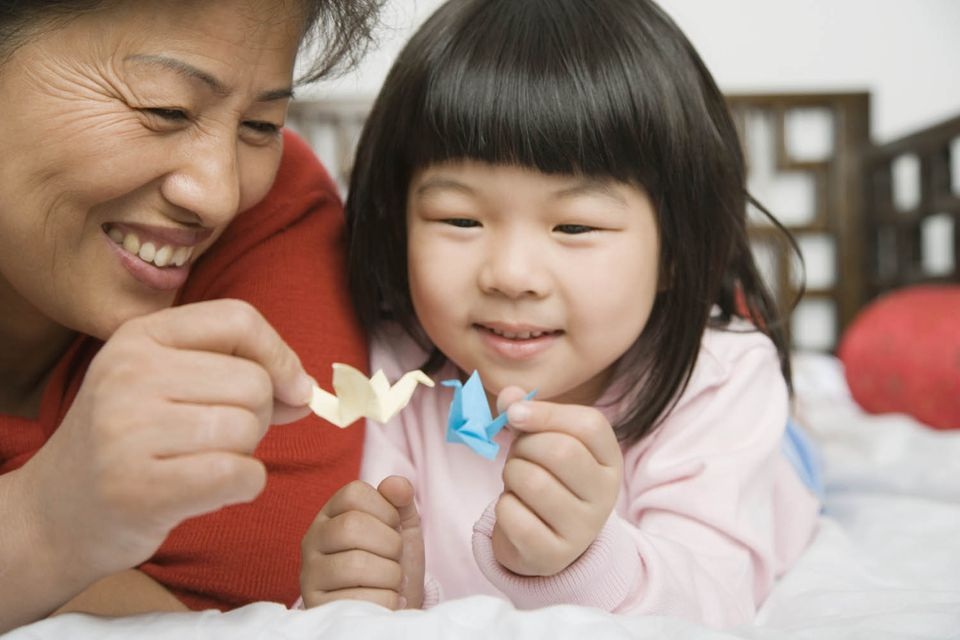 Mother and child holding origami cranes