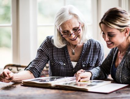 two women looking at a photo album