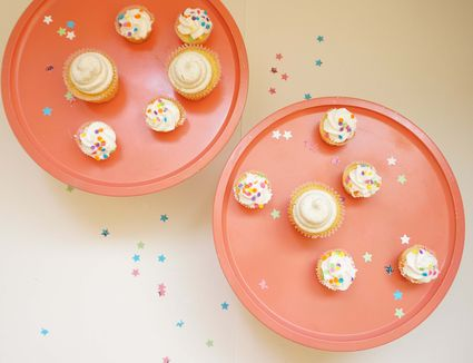 Pink cupcake trays with vanilla cupcakes and confetti.