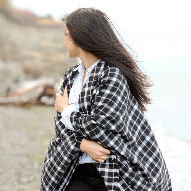 A woman on a beach wearing a black and white cape scarf