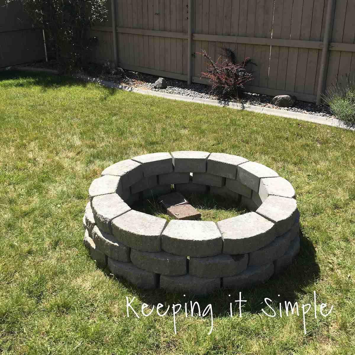 A stone fire pit in a backyard