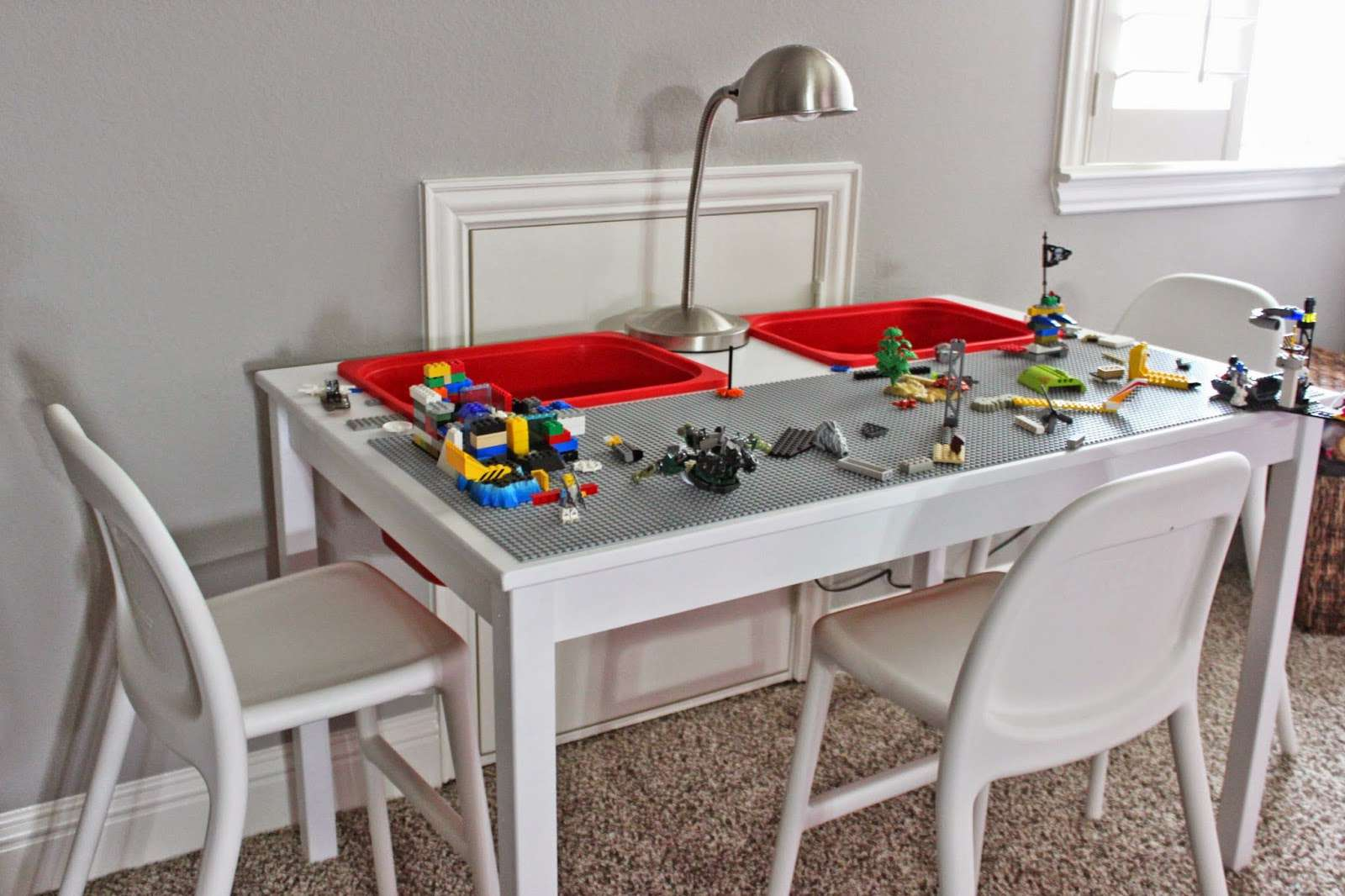 A Lego table with chairs and bins
