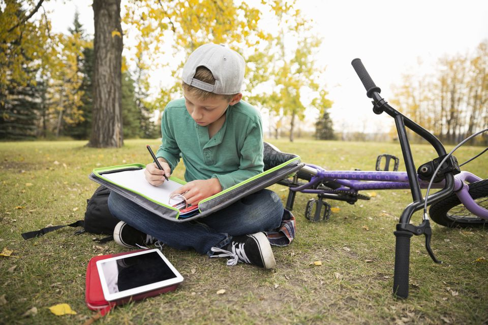 Tween boy doing homework in autumn park
