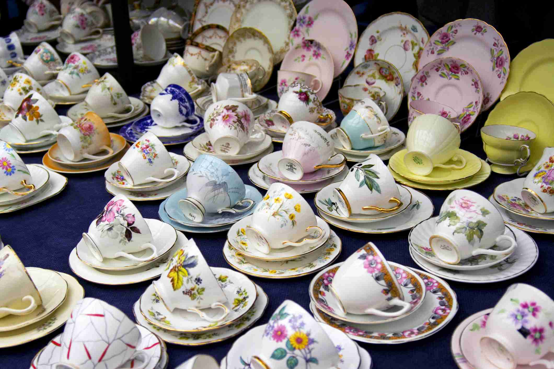 Dozens of teacups, saucers, and plates on a table.