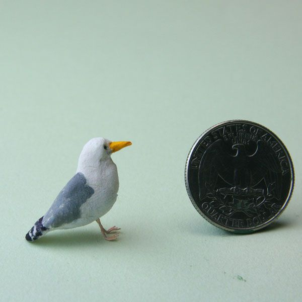 The wire legs and feet of a miniature seagull are set in place under its body.