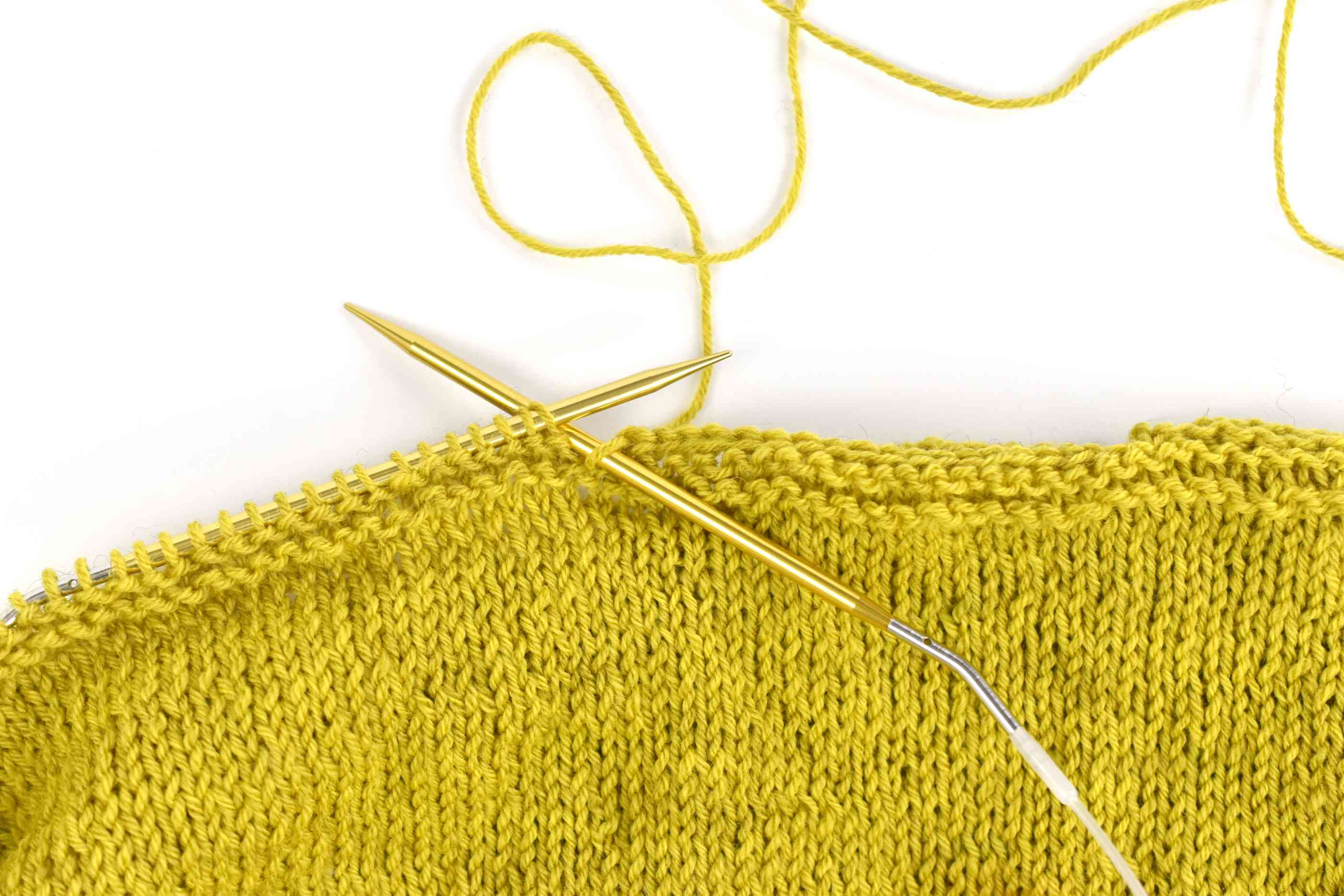 Two knitting needles in chartreuse yarn