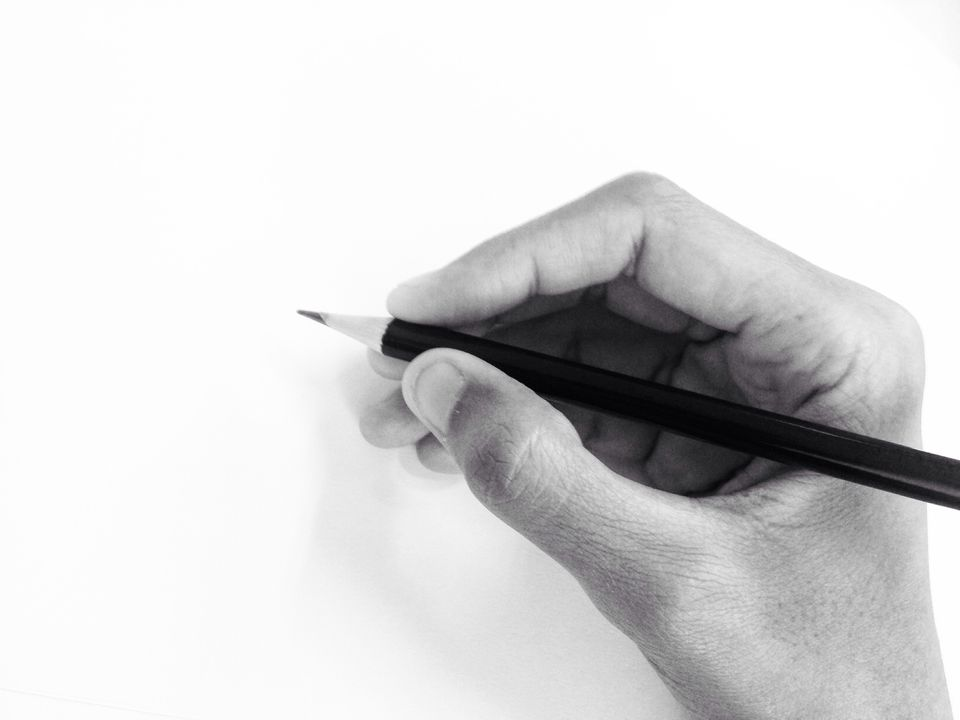 Cropped Hand Of Person Holding Pencil By White Wall
