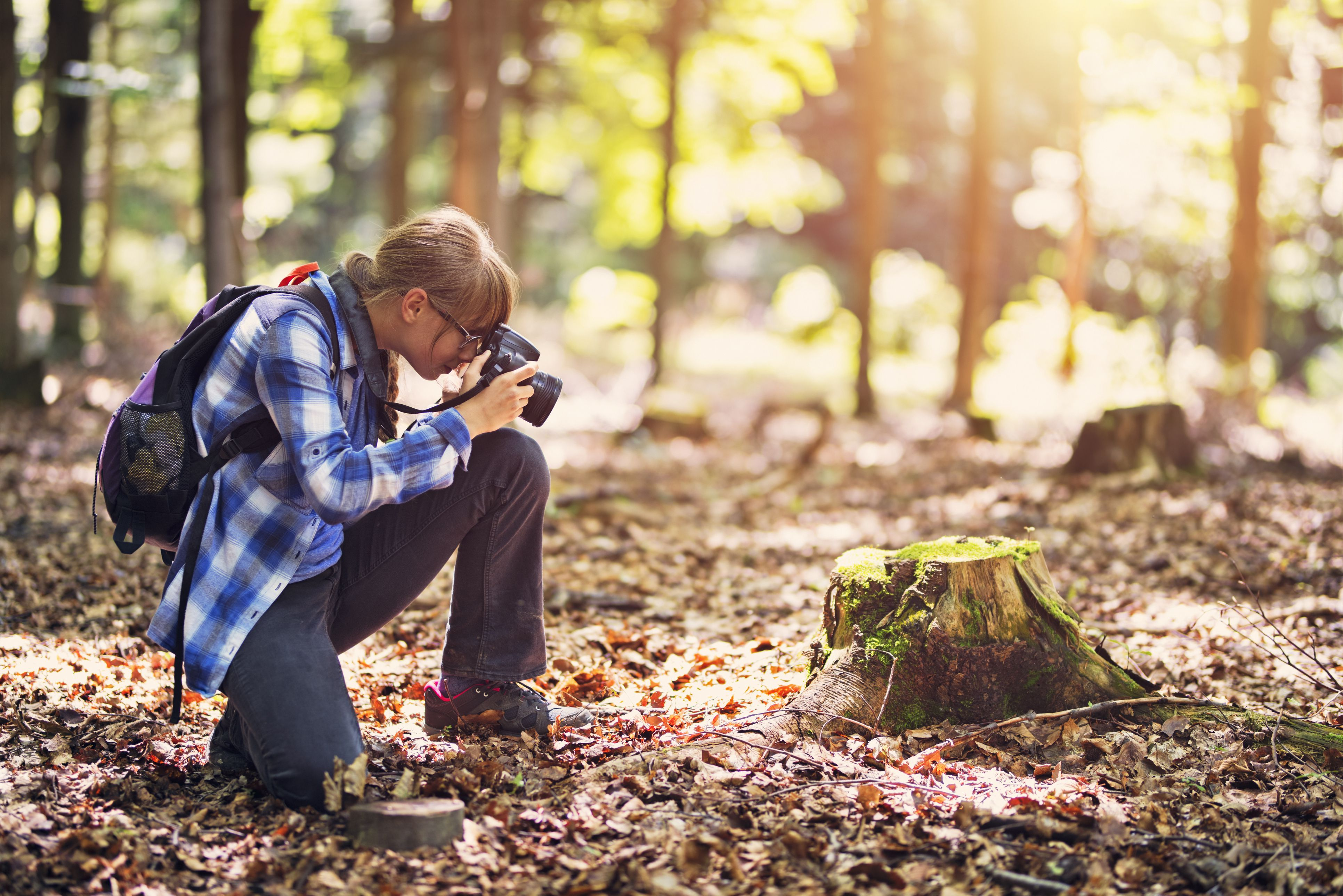 Littel girl photographing in forest