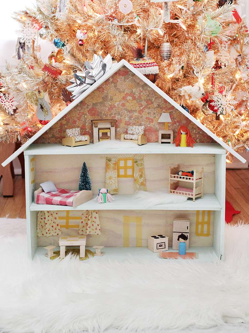 A dollhouse in front of a Christmas tree