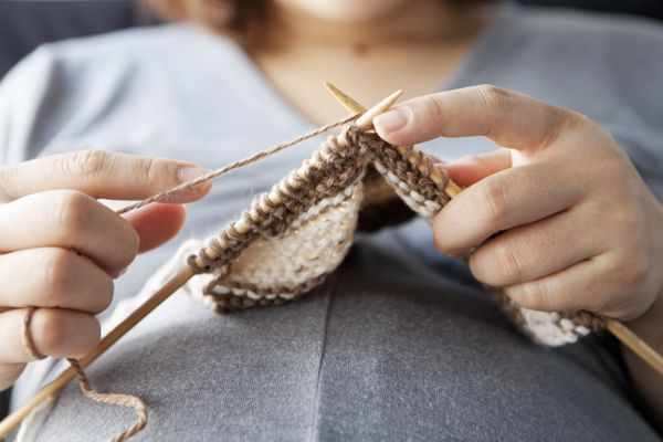 a pregnant woman knitting at home