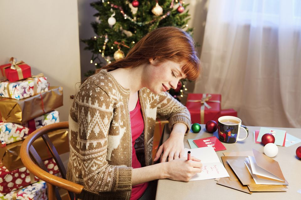 A woman writing Christmas cards