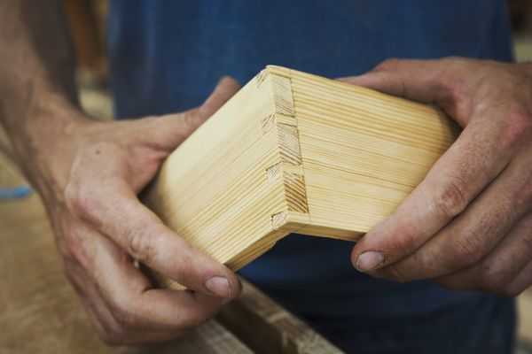 Close up of person working a boat-builders workshop, joining together two pieces of wood.