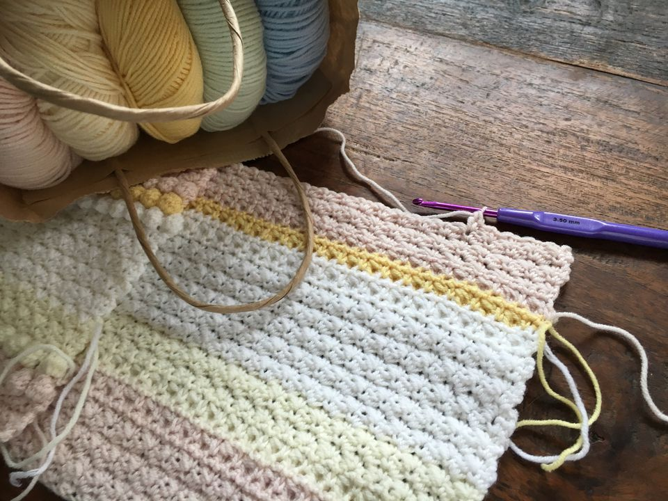 Pastel colored baby blanket in progress with balls of yarn.