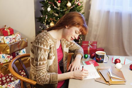 a woman writing christmas cards - Create Christmas Cards