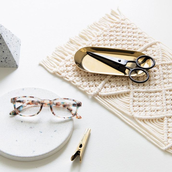 A macrame laptop mat with scissors and reading glasses
