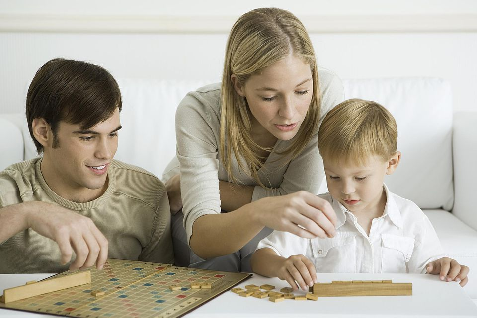 Mother and Father teaching young son to play Scrabble