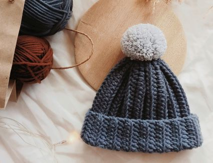 a crochet hat with a pom