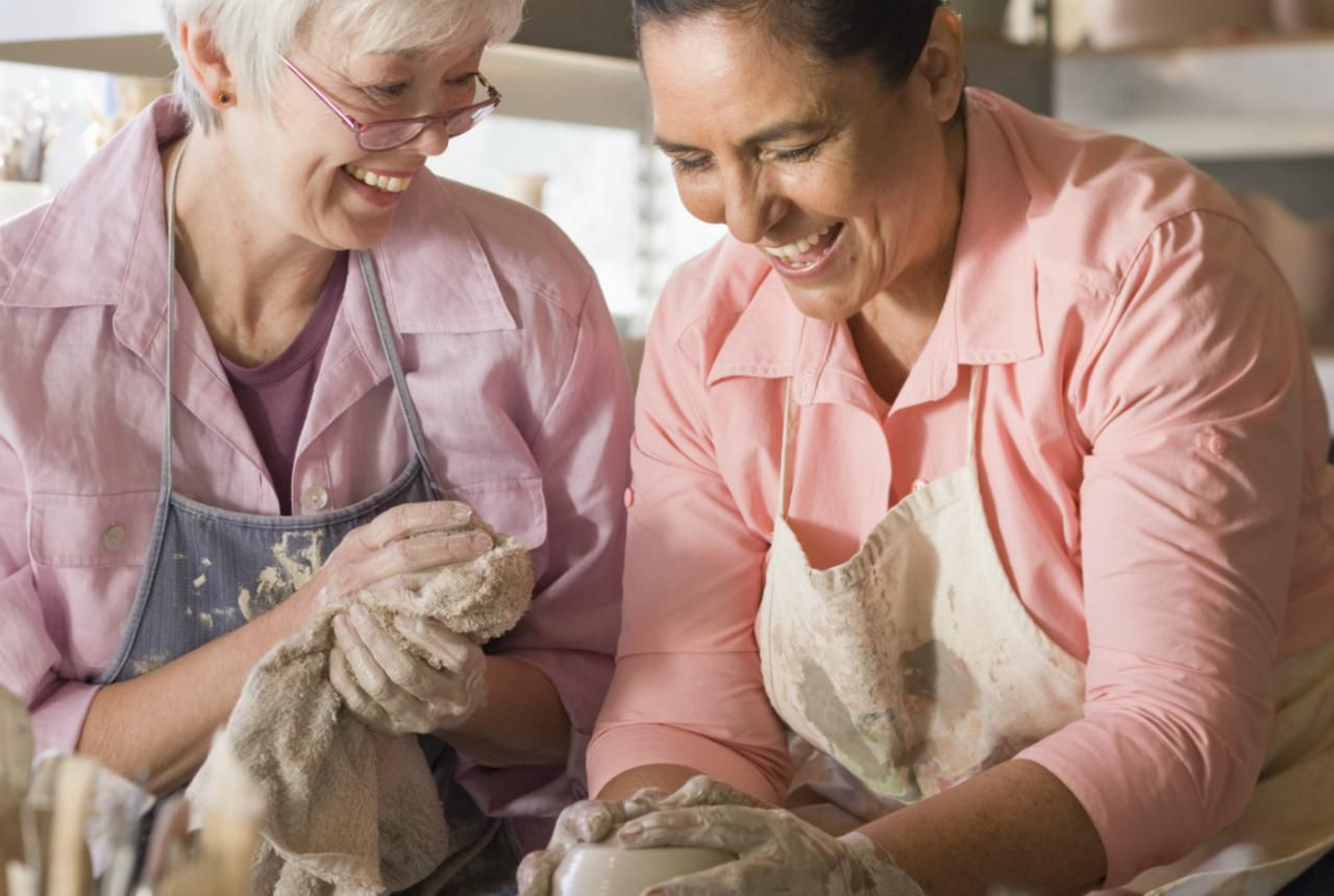 Two potters cleaning their hands on a towel