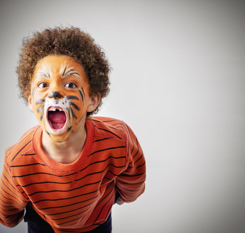 Mixed race boy roaring in tiger face paint