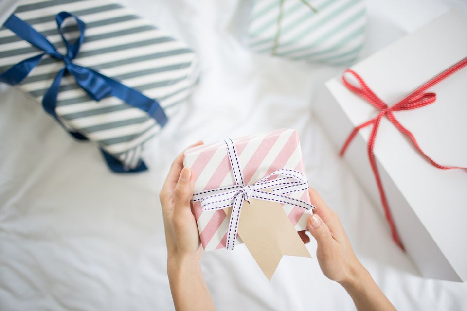 female hand holding gift box with gift tag on the bed