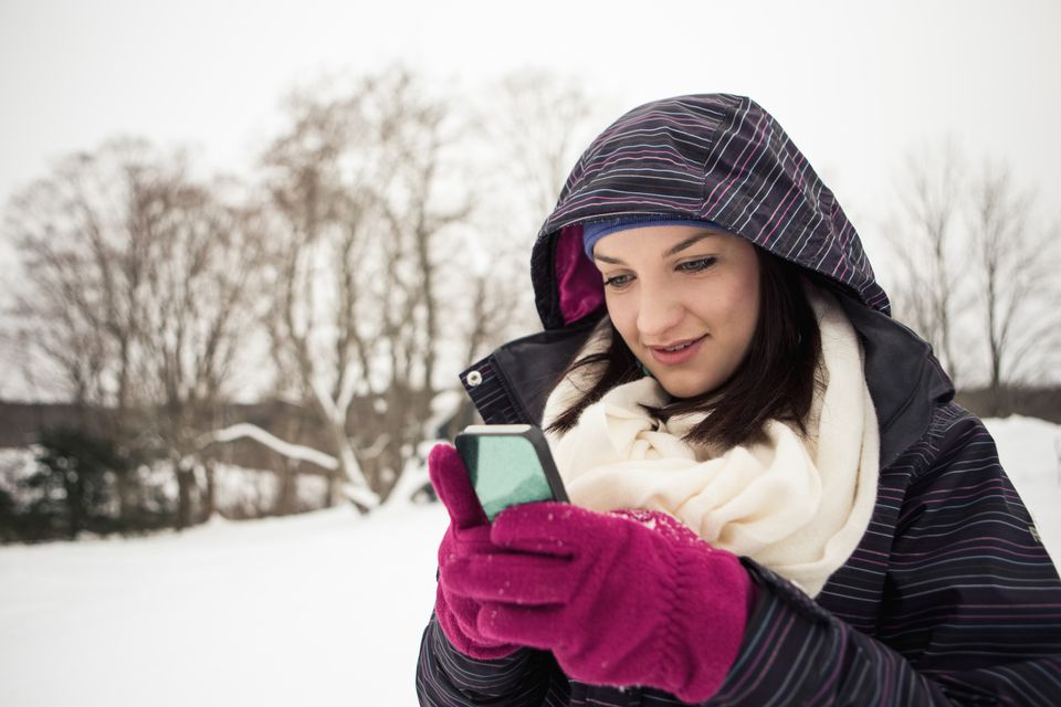 Woman Texting Outside in the Snow With Gloves On
